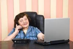 Elderly executive using laptoop and talk by phone. Smiling elderly executive woman talking by telephone and using laptop in her office, check also royalty free stock images