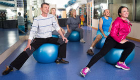 Elderly exercise with gymnastic balls in modern gym. Active elderly exercise with gymnastic balls in modern gym Stock Image