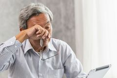 Elderly eye irritation problem fatigue and tired from hard work or computer vision syndrome. Asian elderly eye irritation problem fatigue and tired from hard royalty free stock photography