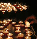 Elderly faithful hand lights a candle Stock Image