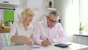 Elderly family calculating home finance in kitchen. Senior wife giving paper to mature husband who counting money stock footage