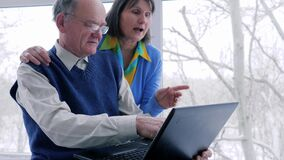 Elderly family online shopping with laptop spend time on internet on holiday at home. Near window stock footage