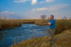 Elderly farmer looking over a river Stock Photos