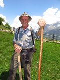 Elderly farmer shepherd Italian Alps spring summer. South Tirol, Italy - June 17, 2013: A smiling shepherd in the Italian Alps leans on a wooden staff in a green Stock Photography