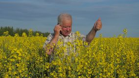 An elderly farmer stands in a field and swears while talking on the phone. stock video footage