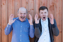 The elderly father-in-law and the young brother-in-law shout in terror, shaking hands. Royalty Free Stock Photos