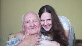 Elderly father sitting in a chair looking out the window and daughter hugging stock footage