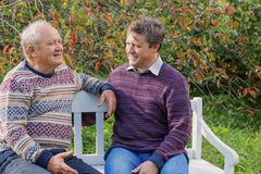 Elderly father and son on bench in autumn park royalty free stock image