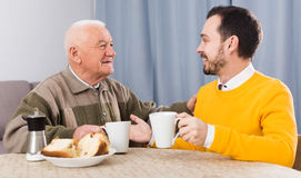 Elderly father and son breakfast. Aged father and his son drinking coffee and talking at table at home stock photography