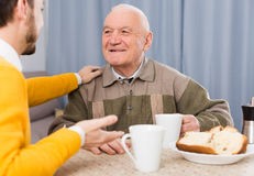 Elderly father and son breakfast. Aged father and his son drinking coffee and talking at table at home Royalty Free Stock Photography