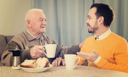 Elderly father and son breakfast. Elderly father and son together having breakfast at table and friendly communicate stock photography