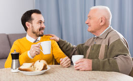 Elderly father and son breakfast. Elderly father and son together having breakfast at table and friendly communicate Royalty Free Stock Photos