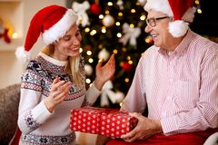 Elderly father surprises his daughter with Christmas gifts Stock Photo