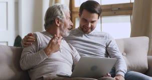 Elderly father talk to son discuss online news using laptop