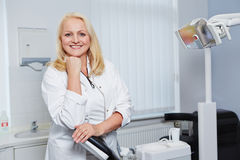 Elderly female dentist in dental practice Stock Photos