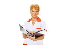 Elderly female doctor or nurse holds black binder and reads.  Stock Photo