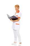 Elderly female doctor or nurse holds black binder and reads.  Royalty Free Stock Images