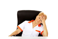 Elderly female doctor or nurse sitting behind the desk with headache Royalty Free Stock Photos