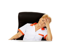 Elderly female doctor or nurse sitting behind the desk with headache Stock Image
