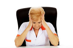 Elderly female doctor or nurse sitting behind the desk with headache Royalty Free Stock Image