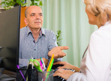 Elderly female  doctor talking with mature male patient Royalty Free Stock Photo