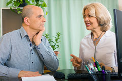 Elderly female  doctor talking with mature male patient Stock Photos