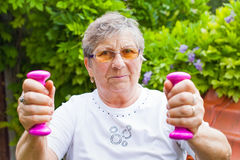 Elderly female exercising with dumbbells Stock Images
