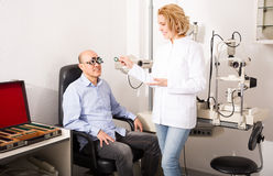 Elderly female ophthalmologist and male pensioner checking eyesi Royalty Free Stock Photos
