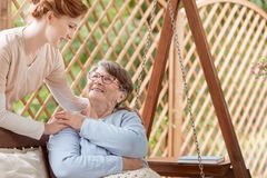 An elderly female pensioner with disabilities sitting on a patio. Swing during rehabilitation camp. Professional caretaker standing next to the woman. Wooden royalty free stock photos