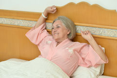 Elderly female  resting in bed Royalty Free Stock Images