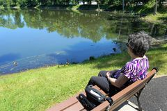 Older woman sits on bench with oxygen tank looking at pond Stock Photography