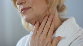 Elderly female touching her face and neck, applying cream, femininity beauty. Stock footage stock video footage