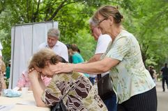 Elderly female volunteer doing relaxing massage to another elderly woman in park stock photography