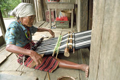 Elderly female weaver works for tourism industry Stock Photography