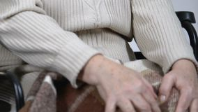 Elderly female in wheelchair massaging knees suffering strong pain in joints. Stock footage stock footage