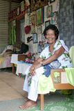 Elderly Fijian woman in home with christian altar and pictures of Jesus, Fijian home with religious photos and saints sculptures Stock Photos