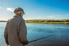 An elderly fisherman on a fishing trip. Old fisherman on the river with a fishing rod Royalty Free Stock Photos