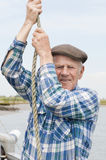 Elderly Fisherman Hauling Rope Royalty Free Stock Photos