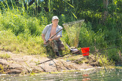 Elderly fisherman landing a fish in a fish net. Elderly handicapped one legged fisherman landing a fish in a long handled fish net as he spends a day fishing on royalty free stock photography