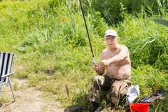 Elderly fisherman reeling in a small fish Stock Photos