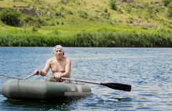 Elderly fisherman rowing across a lake Stock Images
