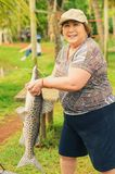 Elderly fisherwoman holding a Pintado fish, looking forward and Royalty Free Stock Image