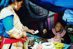 elderly flower hmong tribe member woman selling local natural remedies and medicine on the village farmer market stock images