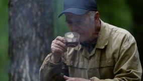 elderly forester is resting in forest and drinking tea near campfire, halt in woodland