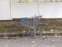 Elderly forgetful person leaves shopping cart on street. On cloudy day Stock Photography