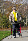Elderly Friend Exercising in Park 2. Elderly Friend with Parkinson's Disease Exercising in Park with a Walker Stock Image