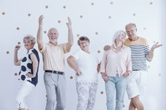 Elderly friends dancing and talking. At a casual new year`s party with gold dots wallpaper stock photography