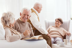 Elderly friends at resting home. Enjoying time drinking tee, talking, and reading Royalty Free Stock Photo