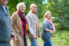 Walking at Park with Friends. Elderly friends wearing knitted sweaters enjoying fresh air and picturesque view while walking along park alley Stock Photography