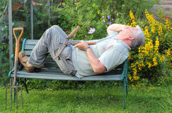 Elderly gardener sleeping on the job. Stock Image